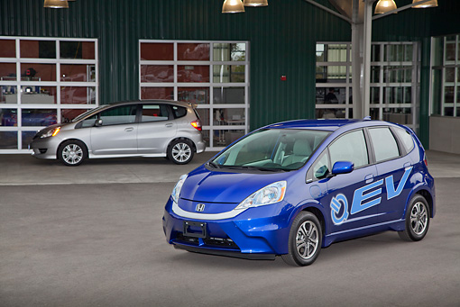 AUT 48 RK0064 01 © Kimball Stock 2012 Honda Fit EV Blue 3/4 Front View On Pavement By Building