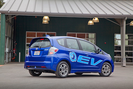 AUT 48 RK0065 01 © Kimball Stock 2012 Honda Fit EV Blue 3/4 Rear View On Pavement By Building