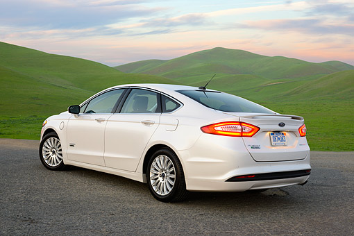 AUT 49 RK0015 01 © Kimball Stock 2013 Ford Fusion Energi Titanium White 3/4 Rear View On Pavement By Grassy Hills