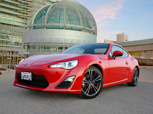 AUT 49 RK0018 01 © Kimball Stock 2013 Scion FR-S Red 3/4 Front View On Pavement By Building