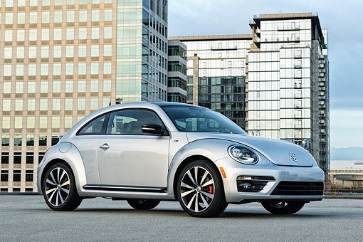 AUT 50 BK0008 01 © Kimball Stock 2014 Volkswagen Beetle Silver 3/4 Side View On Concrete By Glass Buildings