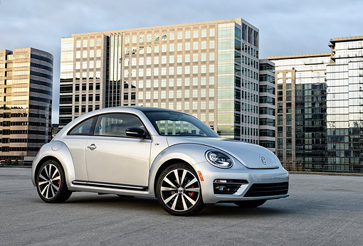 AUT 50 BK0009 01 © Kimball Stock 2014 Volkswagen Beetle Silver 3/4 Side View On Concrete By Glass Buildings