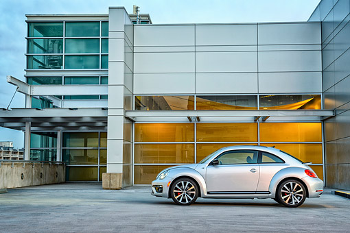 AUT 50 BK0011 01 © Kimball Stock 2014 Volkswagen Beetle Silver Profile View On Concrete By Glass Building