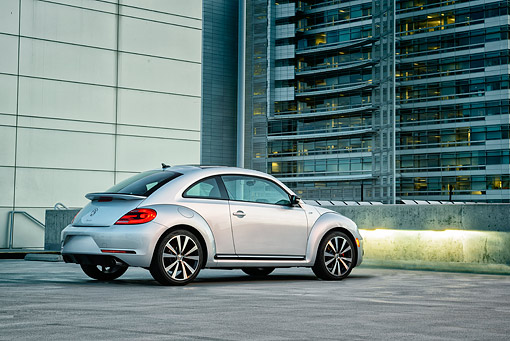 AUT 50 BK0013 01 © Kimball Stock 2014 Volkswagen Beetle Silver 3/4 Rear View On Concrete By Glass Building