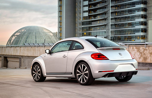 AUT 50 BK0014 01 © Kimball Stock 2014 Volkswagen Beetle Silver 3/4 Rear View On Concrete By Buildings