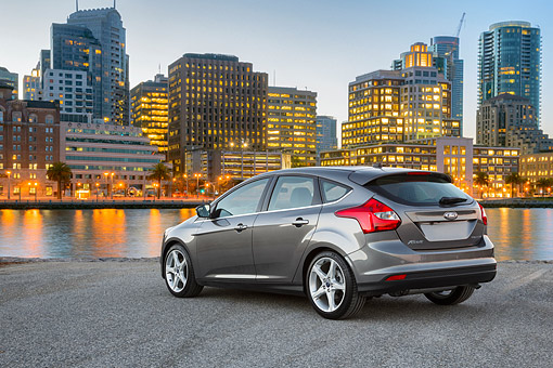AUT 50 BK0017 01 © Kimball Stock 2014 Ford Focus Titanium Gray 3/4 Rear View On Pavement By City At Dusk