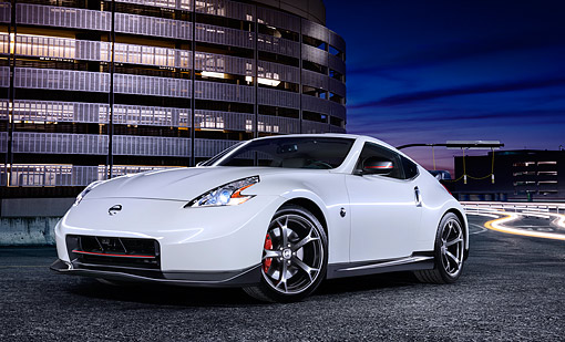 AUT 50 BK0022 01 © Kimball Stock 2014 Nissan Nismo White 3/4 Front View On Pavement By Building At Night