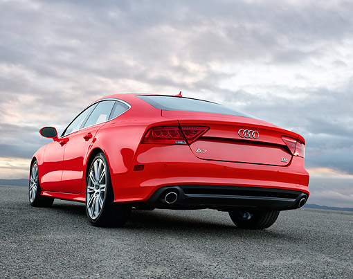AUT 50 BK0027 01 © Kimball Stock 2014 Audi A7 Red Low 3/4 Rear View On Pavement In Evening Under Clouds