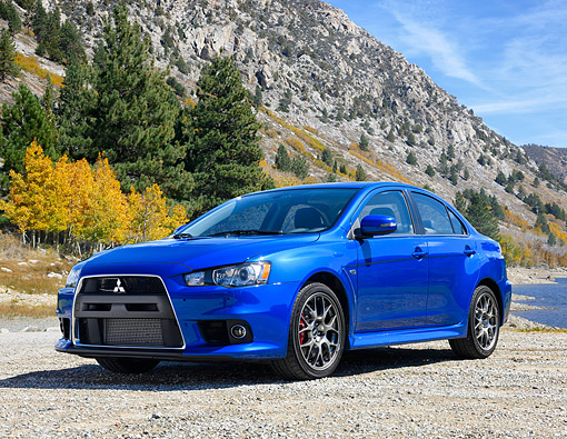AUT 51 RK0073 01 © Kimball Stock 2015 Mitsubishi Lancer Evolution Blue 3/4 Front View On Lake By Mountain
