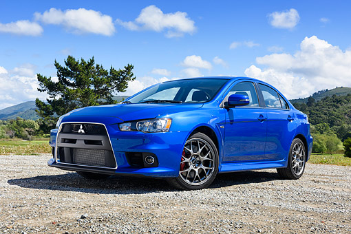 AUT 51 RK0074 01 © Kimball Stock 2015 Mitsubishi Lancer Evolution Blue 3/4 Front View On Lake By Trees