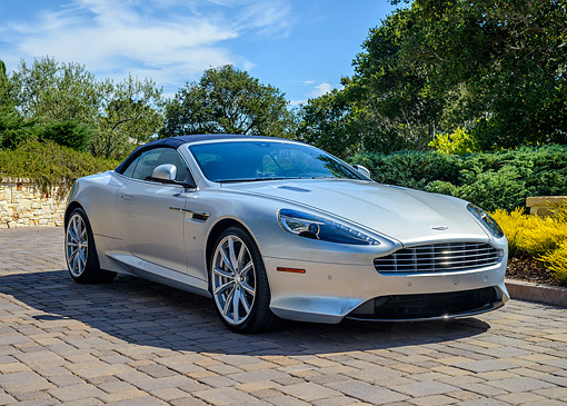 AUT 51 RK0089 01 © Kimball Stock 2015 Aston Martin DB9 Silver Convertible 3/4 Front View By Trees And Bushes