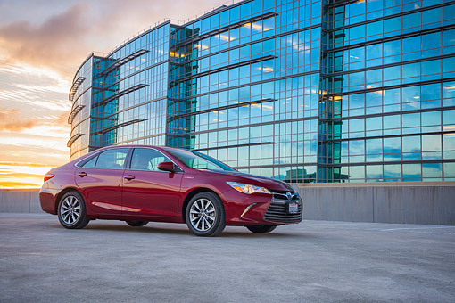 AUT 52 RK0036 01 © Kimball Stock 2016 Toyota Camry Hybrid Maroon 3/4 Front View On Pavement By Building