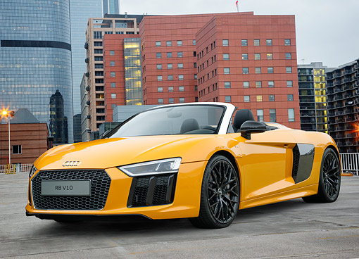 AUT 53 RK0005 01 © Kimball Stock 2017 Audi R8 V10 Spyder Yellow 3/4 Front On Pavement By Buildings