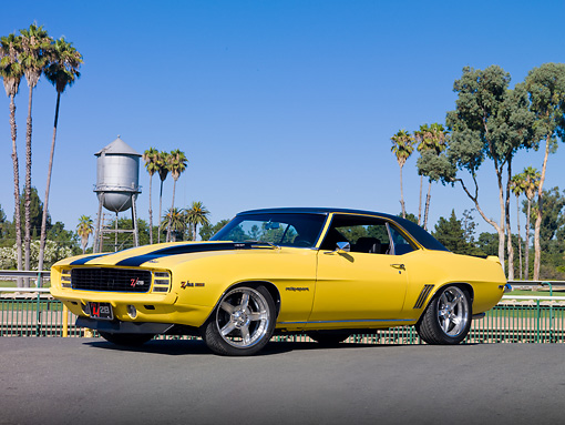 CAM 01 RK0220 01 © Kimball Stock 1969 Chevrolet Camaro Z-28 Yellow With Black Stripes 3/4 Front View On Pavement By Palm Trees And Water Tower