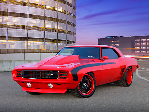 CAM 01 RK0274 01 © Kimball Stock 1969 Chevrolet Camaro Z-28 Red 3/4 Front View On Pavement By Parking Garage At Dusk