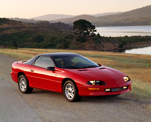 CAM 01 RK0049 02 © Kimball Stock 1993 Chevrolet Camaro Z-28 Red 3/4 Front View On Dirt Road Lake Background