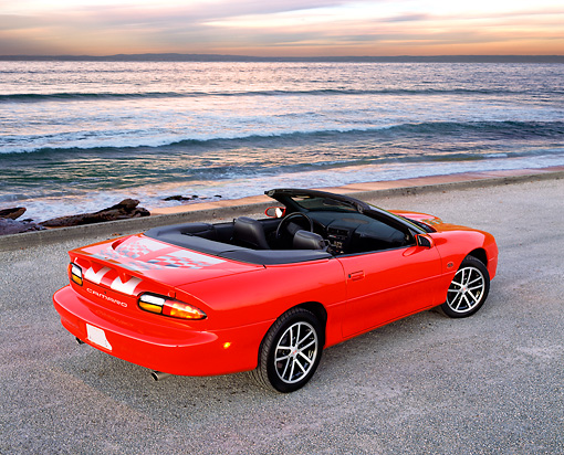 CAM 01 RK0142 01 © Kimball Stock 2002 Chevrolet Camaro SS 35th Anniversary Editon Convertible Red And Silver 3/4 Rear View On Beach