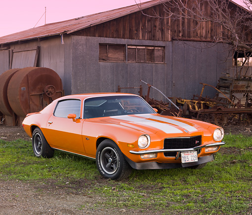 CAM 01 RK0164 01 © Kimball Stock 1970 Chevrolet Camaro Z-28 Hugger Orange And White Stripe 3/4 Front View On Grass By Barn