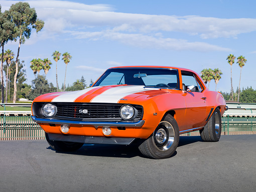 CAM 02 RK0069 01 © Kimball Stock 1969 Chevrolet Camaro SS Orange With White Stripes 3/4 Front View On Pavement By Palm Trees And Water Tower