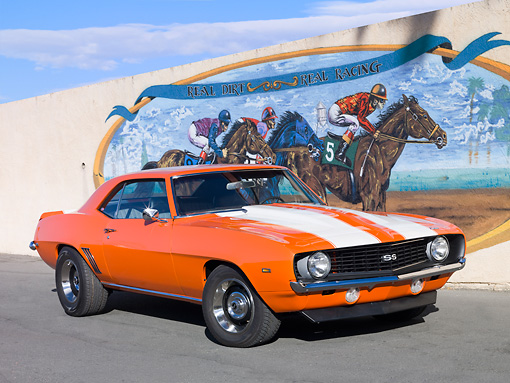 CAM 02 RK0070 01 © Kimball Stock 1969 Chevrolet Camaro SS Orange With White Stripes 3/4 Front View On Pavement By Horse Racing Mural