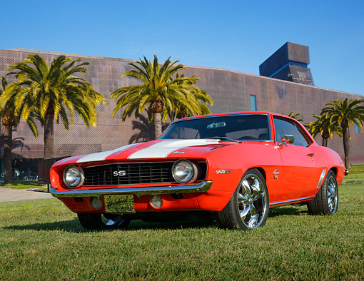 CAM 02 RK0182 01 © Kimball Stock 1969 Chevrolet Camaro SS Red With White Stripes 3/4 Front View On Grass By Palm Trees And Building