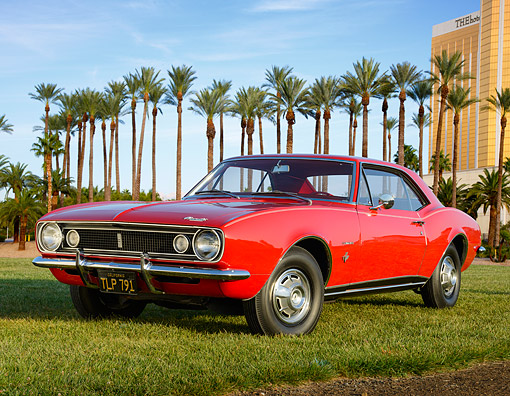 CAM 02 RK0184 01 © Kimball Stock 1967 Chevrolet Camaro Red 3/4 Front View On Grass By Palm Trees And Building