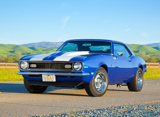 CAM 03 BK0001 01 © Kimball Stock 1968 Chevrolet Camaro Blue With White Stripe 3/4 Front View On Road By Grassy Hills