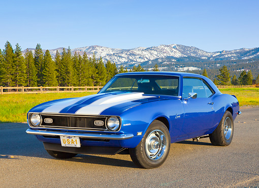 CAM 03 BK0002 01 © Kimball Stock 1968 Chevrolet Camaro Blue With White Stripe 3/4 Front View On Road By Pine Trees And Snow-Covered Mountains