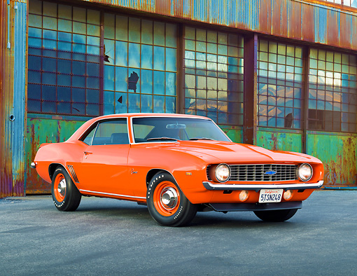 CAM 03 RK0222 01 © Kimball Stock 1969 Chevrolet COPO Camaro Orange 3/4 Front View On Pavement By Old Factory Building