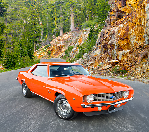 CAM 03 RK0226 01 © Kimball Stock 1969 Chevrolet Camaro ZL-1 Orange 3/4 Front View On Pavement By Trees And Rocky Cliffside