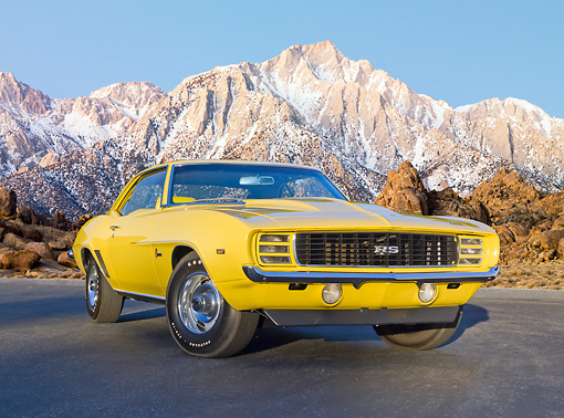 CAM 03 RK0239 01 © Kimball Stock 1969 Chevrolet COPO Camaro RS Yellow 3/4 Front View On Pavement By Snowy Mountains