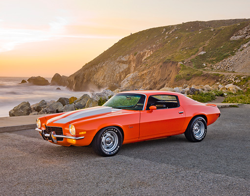 CAM 04 RK0138 01 © Kimball Stock 1973 Chevrolet Camaro Orange And White Stripes 3/4 Front View On Pavement By Sand Dune