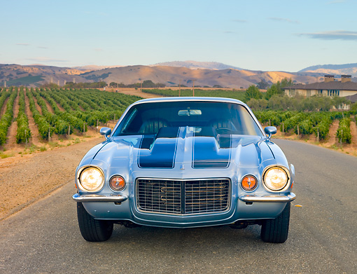 CAM 04 RK0161 01 © Kimball Stock 1972 Chevrolet Camaro RS Blue With Black Stripes Head On View On Road By Vineyards