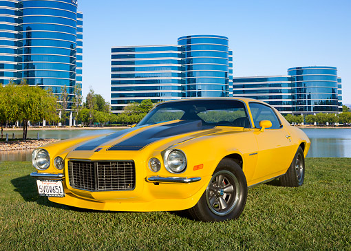 CAM 04 RK0252 01 © Kimball Stock 1971 Chevrolet Camaro High Velocity Yellow With Charcoal Pearl Stripes 3/4 Front View On Grass By Glass Buildings