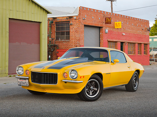 CAM 04 RK0253 01 © Kimball Stock 1971 Chevrolet Camaro High Velocity Yellow With Charcoal Pearl Stripes 3/4 Front View On Pavement By Brick Building