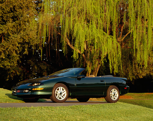 CAM 04 RK0018 01 © Kimball Stock 1994 Chevrolet Camaro Z-28 Convertible Green 3/4 Front View By Trees And Grass