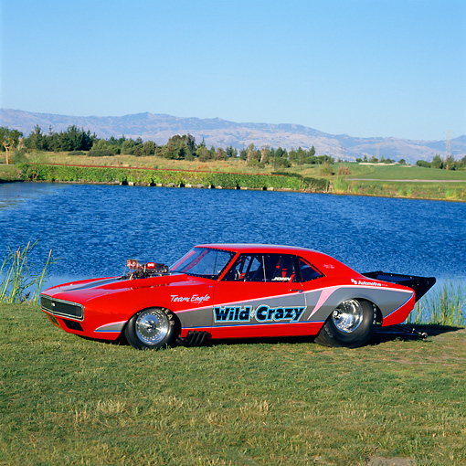 CAM 04 RK0033 04 © Kimball Stock 1967 Red & Black Chevy Camaro Blow Fuel Dragster 3/4 Front View On Grass By Water And Trees