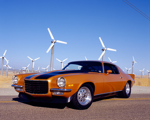 CAM 04 RK0067 01 © Kimball Stock 1973 Chevrolet Camaro Gold Black Stripe Low 3/4 Front View On Road By Wind Turbines