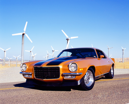 CAM 04 RK0069 03 © Kimball Stock 1973 Chevrolet Camaro Gold Black Stripe Low 3/4 Front View On Road By Wind Turbines