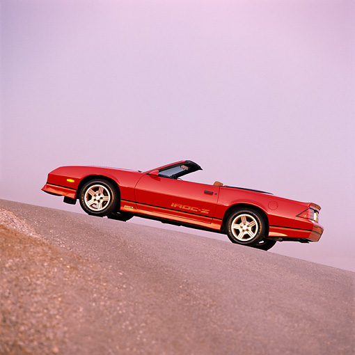 CAM 06 RK0004 08 © Kimball Stock 1988 Chevrolet Camaro IROC-Z Convertible Red Slanted 3/4 Rear View On Pavement Hill