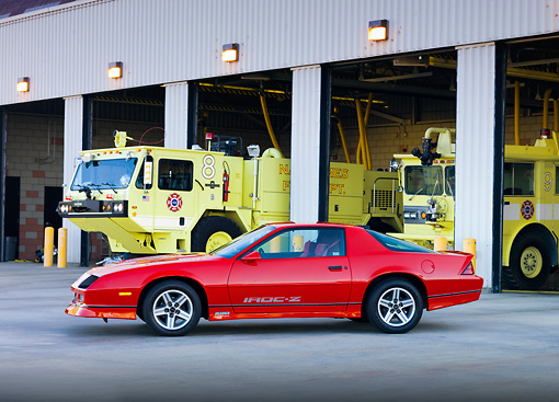 CAM 06 RK0025 01 © Kimball Stock 1986 Chevrolet Camaro IROC-Z Red 3/4 Front View At Fire Station