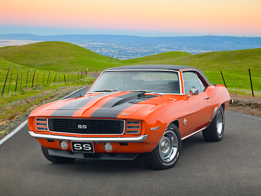 CAM 07 RK0132 01 © Kimball Stock 1969 Chevrolet Camaro RS/SS Hugger Orange With Black Stripes 3/4 Front View On Road By Grassy Hills At Dusk