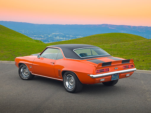 CAM 07 RK0133 01 © Kimball Stock 1969 Chevrolet Camaro RS/SS Hugger Orange With Black Stripes 3/4 Rear View On Road By Grassy Hills At Dusk