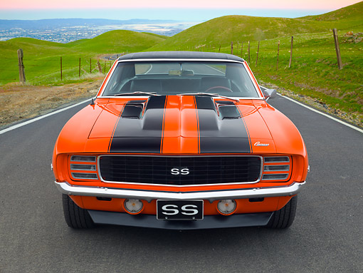 CAM 07 RK0134 01 © Kimball Stock 1969 Chevrolet Camaro RS/SS Hugger Orange With Black Stripes Front View On Road By Grassy Hills At Dusk