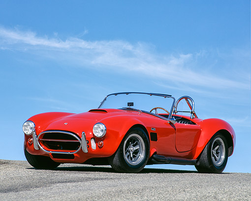 COB 01 RK0008 01 © Kimball Stock 1965 Shelby Cobra 427  Convertible Red 3/4 Front View On Pavement Against Blue Sky