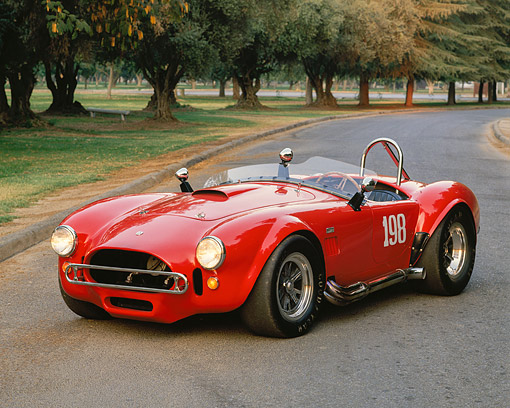 COB 01 RK0066 04 © Kimball Stock 1966 AC Shelby Cobra Race Car Red 3/4 Front View On Road By Trees