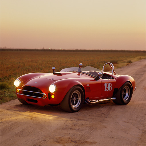 COB 01 RK0075 02 © Kimball Stock 1966 Shelby Cobra Convertible Race Car Red Side 3/4 On Dirt At Dusk
