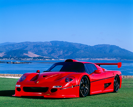 FRR 01 RK0062 04 © Kimball Stock Ferrari F-50 GTR 1 Red 3/4 Front View On Grass By Water Blue Sky