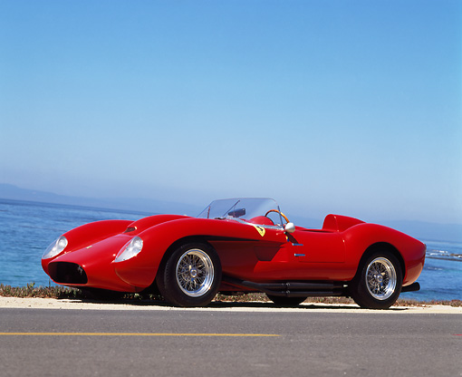 FRR 03 RK0011 01 © Kimball Stock 1958 Ferrari 250 TR Rebody Red 3/4 Front View On Road Ocean Blue Sky