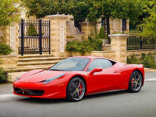 FRR 04 RK0652 01 © Kimball Stock 2011 Ferrari 458 Italia Red 3/4 Side View On Pavement By Gate And Trees